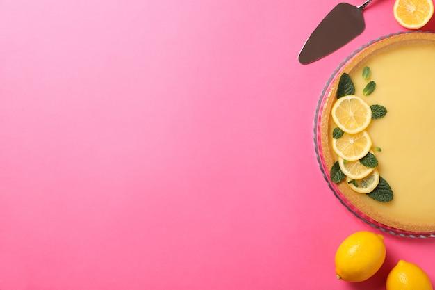 Лимонный пирог, шпатель и лимоны на розовом, вид сверху