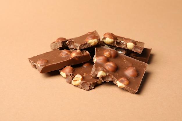 Кусочки шоколада на бежевом фоне. сладкая еда