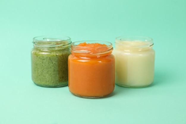 ミントの背景に野菜のピューレが付いているガラス瓶。ベビーフード