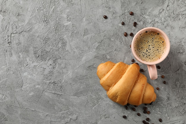 Чашка кофе и круассан на сером фоне, вид сверху