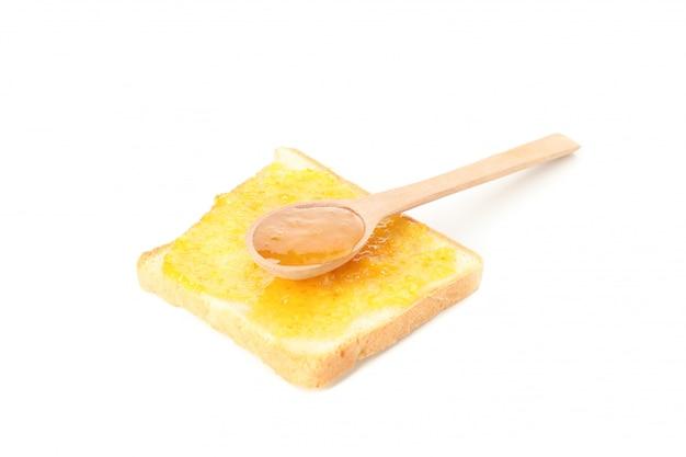 スプーンと白い背景で隔離されたオレンジのジャムとトースト