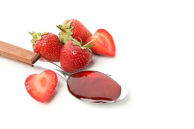 イチゴといちごジャムの白い背景で隔離のスプーン