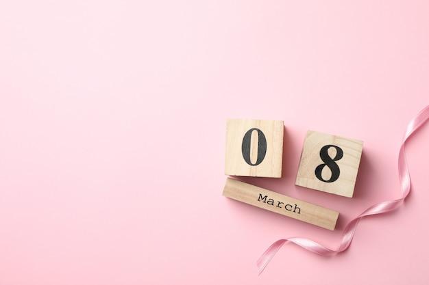 Деревянный календарь и лента на розовом фоне, место для текста