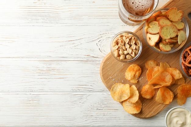 Чипсы, бокал пива, пивные закуски, пивные орехи, соусы на белом деревянные, место для текста. вид сверху