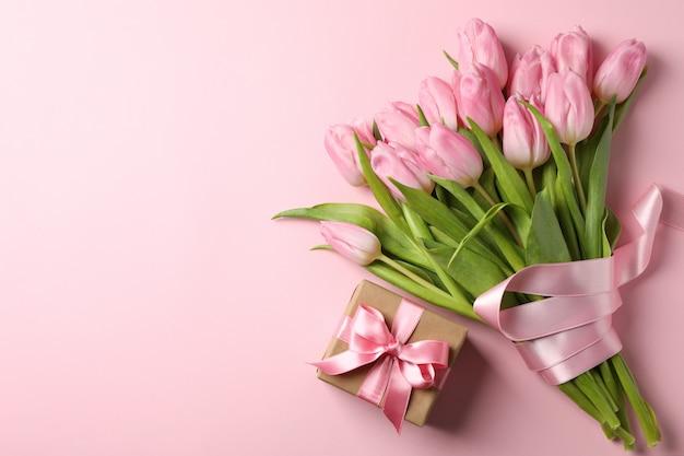 チューリップとピンクの背景、テキスト用のスペースのギフトボックスの花束