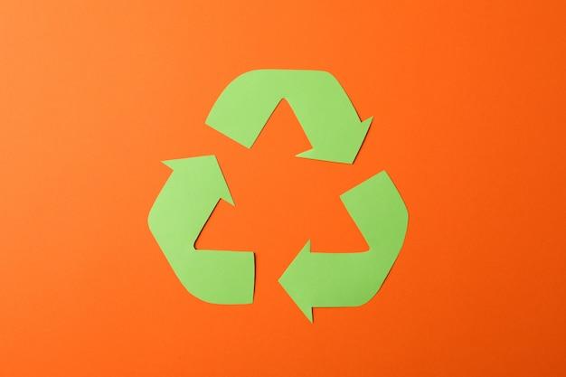 オレンジ色の背景、トップビューでサインをリサイクル