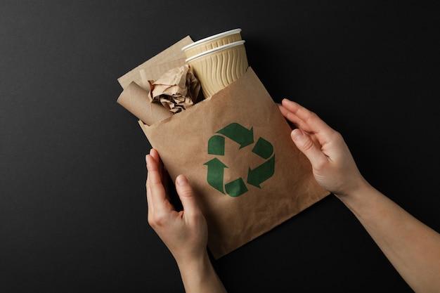 紙のゴミ袋とリサイクルバッグを保持している手黒の背景、上面に署名します。