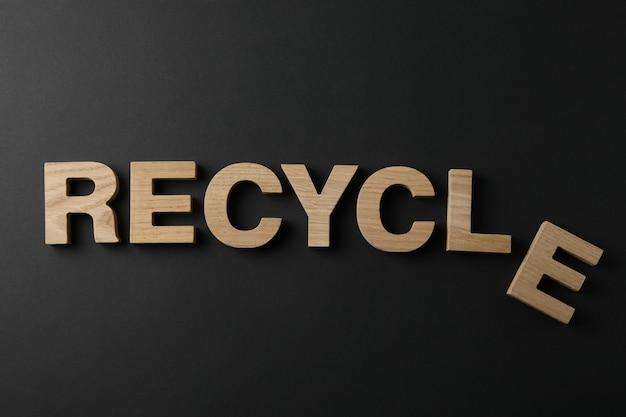 黒の背景、上面に木製の文字で作られた単語のリサイクル