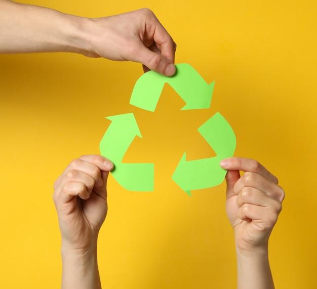 黄色の背景にリサイクルサインを保持している手、クローズアップ