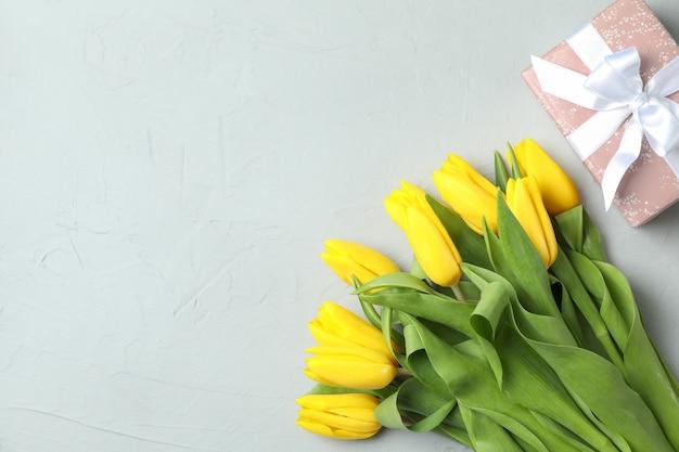 グレー、トップビューで美しい新鮮な黄色のチューリップ。テキストのためのスペース