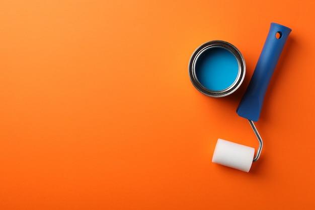 青いペンキとオレンジ色の表面のローラー