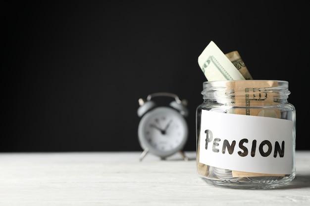 Стеклянная банка с деньгами и будильником на черной поверхности