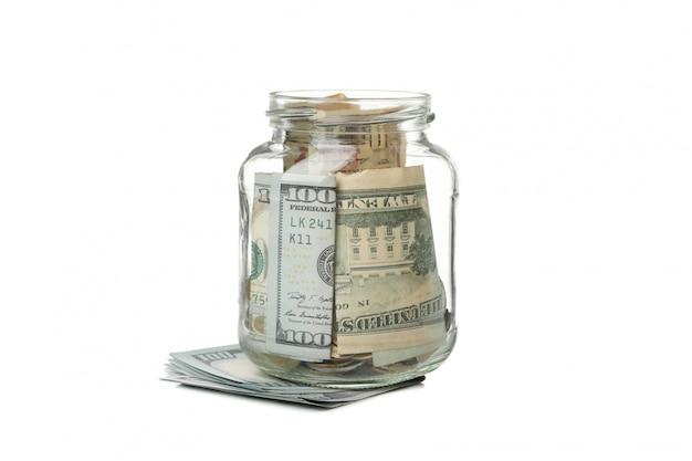 Стеклянная банка с деньгами на белом фоне