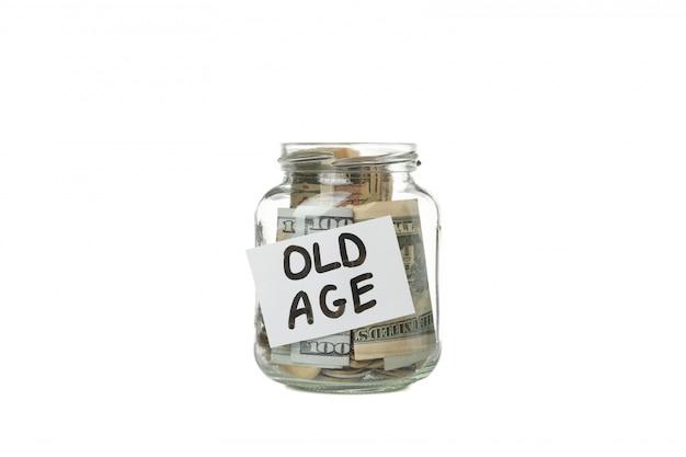Стеклянная банка с деньгами и надписью старости, изолированных на белой поверхности