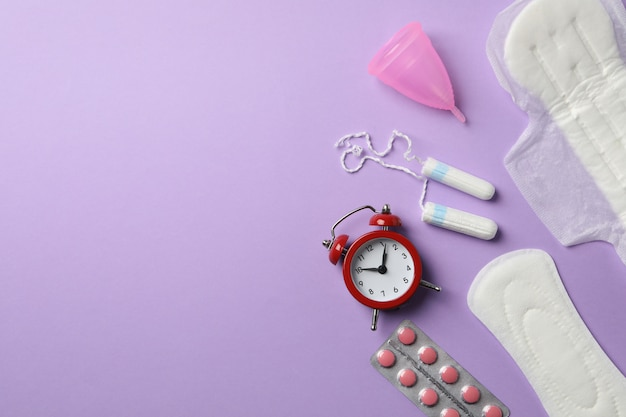Концепция менструального периода на фиолетовой поверхности