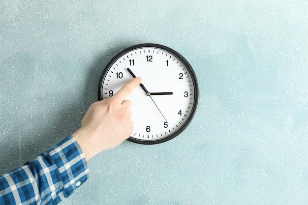 男は美しい壁時計、テキスト用のスペースに時間を変更します。
