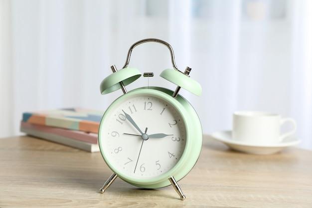 一杯のコーヒー、多肉植物、光に対するテーブルの上の本を持つ美しいレトロな目覚まし時計