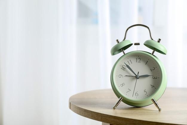 光に対してテーブルの上の美しいレトロな目覚まし時計