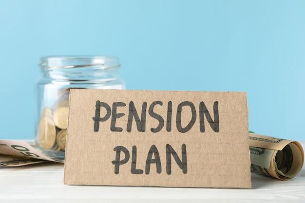 Пенсионный план надпись и банку с деньгами на синем, крупным планом