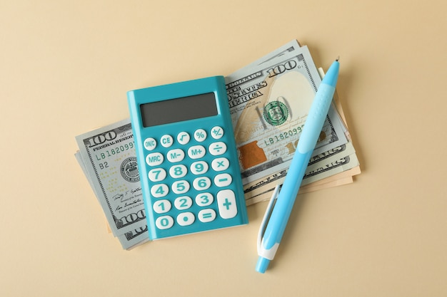 Деньги, калькулятор и ручка на бежевом, вид сверху