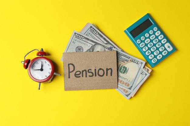 Надпись пенсия, деньги, калькулятор и будильник на желтом, вид сверху