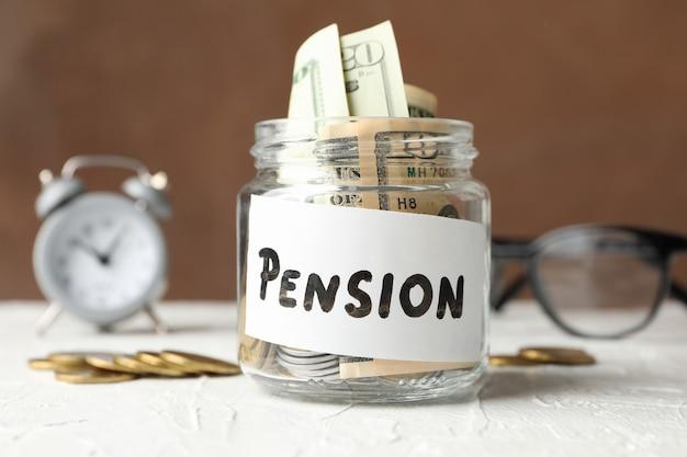 Баночка с деньгами и надписью пенсия против коричневого, крупным планом