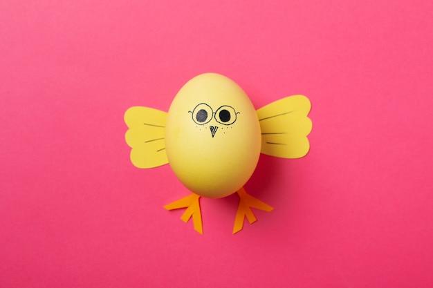 Желтый цыпленок из яйца на розовой поверхности