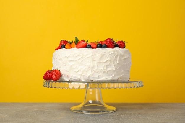 Ягодный кремовый торт на желтом фоне