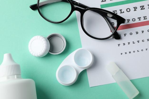 Очки, футляр для контактных линз и карта глазных испытаний на поверхности мяты, вид сверху