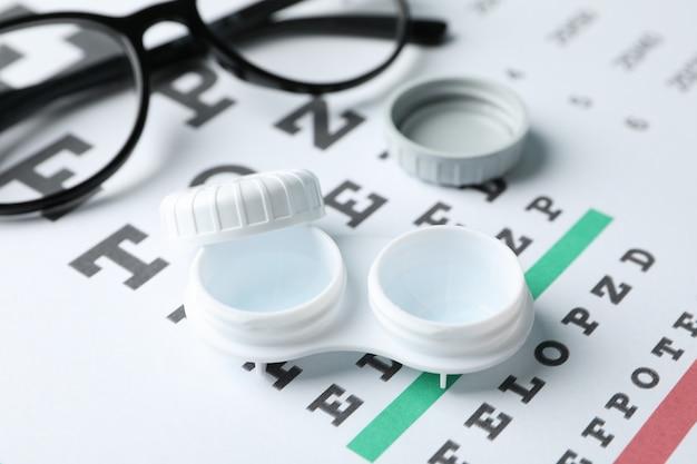 Очки, футляр для контактных линз и таблица глазных испытаний, крупный план