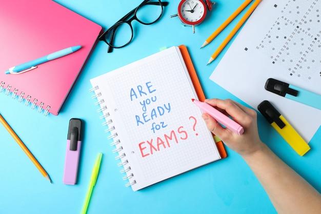 碑文試験の準備はできていますか?女性は青い表面にマーカーを保持します。勉強と試験のコンセプト