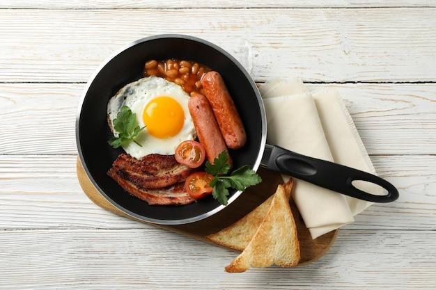 木製のテーブル、上面に目玉焼きとおいしい朝食またはランチ