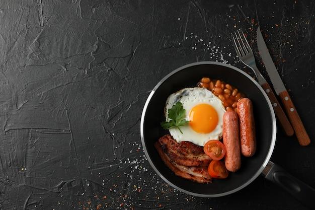 黒の表面、上面に目玉焼きとおいしい朝食またはランチ