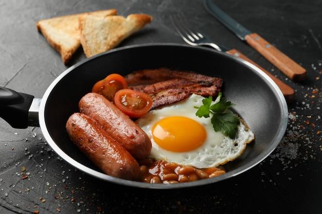 黒い表面に目玉焼きのおいしい朝食またはランチ、クローズアップ