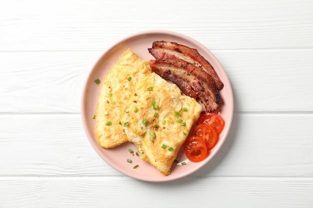 木製のテーブル、トップビューでオムレツとおいしい朝食またはランチ