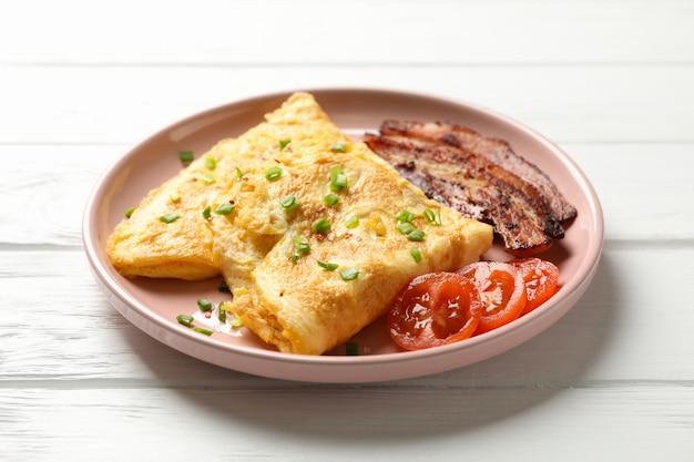 木製のテーブルでオムレツと美味しい朝食やランチ、クローズアップ