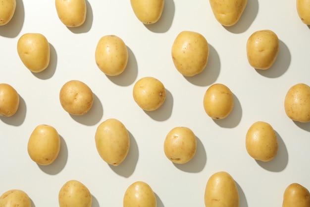 白い表面に若いジャガイモとフラットレイアウト