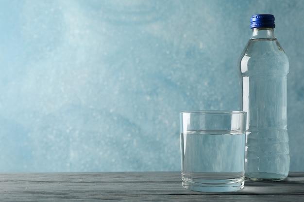 Бутылка с водой и стакан на деревянный стол, место для текста