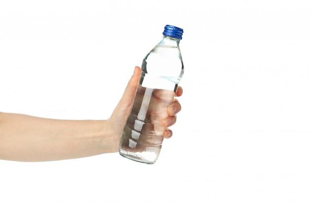 Женская рука держит бутылку с водой, изолированных на белом