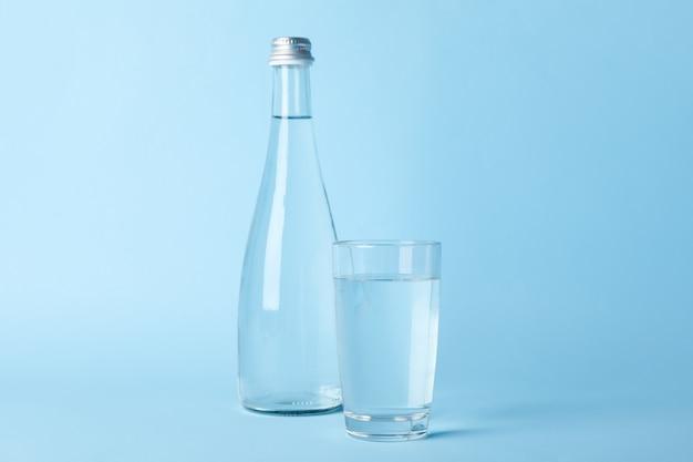 Стекло и бутылка с водой на синем, место для текста