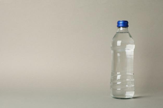 Бутылка с водой на сером, место для текста