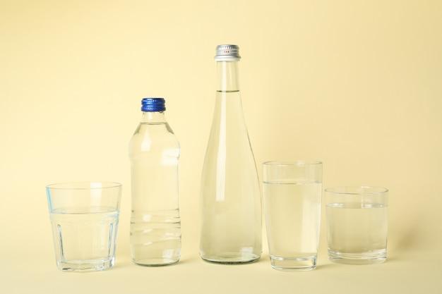 Бутылки и стаканы с водой на бежевом