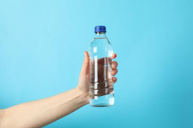 Женская рука держит бутылку с водой на синем, крупным планом