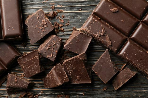 Кусочки шоколада на деревянном, крупный план