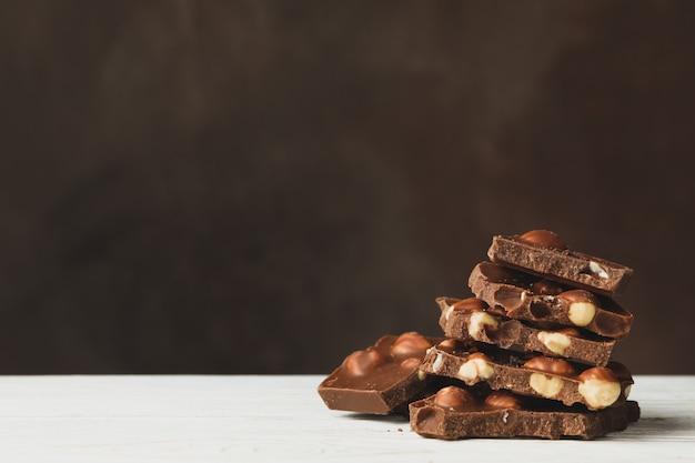 Вкусные кусочки шоколада на белом деревянном столе
