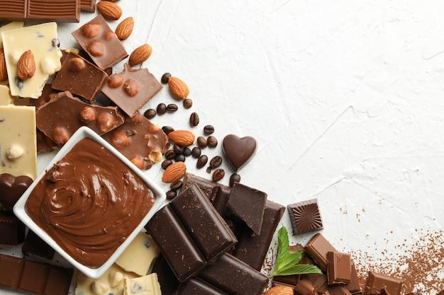 Шоколад, растопленный шоколад, кофе и миндаль на белом