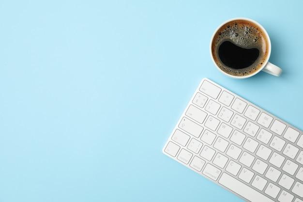 Белая клавиатура и кофе на синем