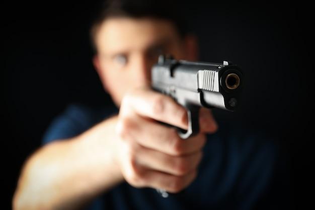 Мужчина держит пистолет. выборочный фокус. оружие самообороны