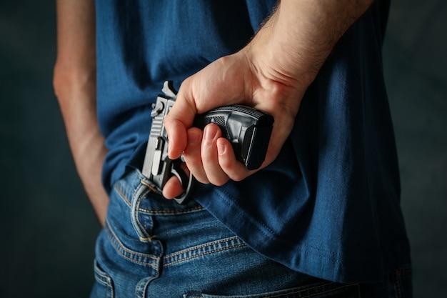 Мужчина держит пистолет сзади. оружие самообороны