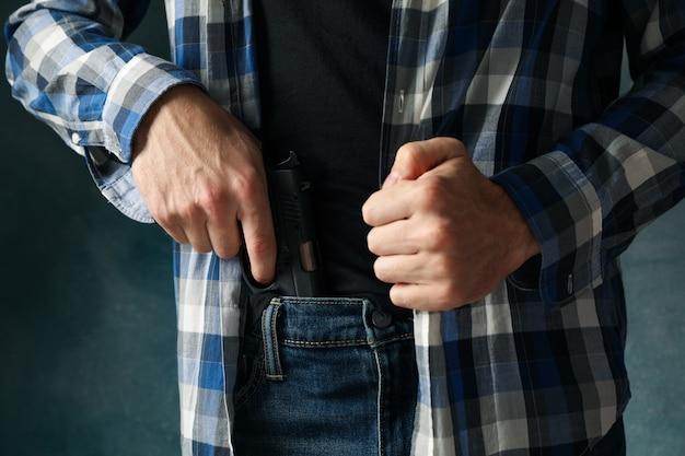 Мужчина достает пистолет из джинсов, крупный план. грабитель